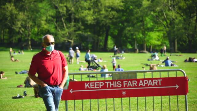 police officers will limit access to the central park sheep meadow to prevent overcrowding - central park manhattan stock videos & royalty-free footage