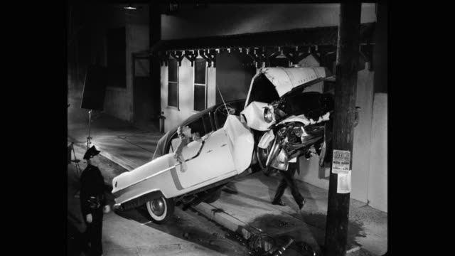 1955 - police official arresting drunk man for car crash on street - traffic accident stock videos & royalty-free footage