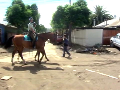 stockvideo's en b-roll-footage met police on horseback ride patrol streets following devastating earthquake in chile 4 march 2010 - recreatief paardrijden