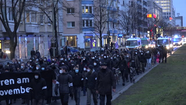 """stockvideo's en b-roll-footage met police patrol as people chant holding a black banner stating """"geboren am 17 november"""" as around 250 protesters march through the friedrichshain area... - geboren in"""