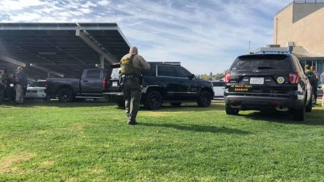 police patrol as students are evacuated from saugus high school after a shooting at the school left two students dead and three wounded on november... - santa clarita video stock e b–roll