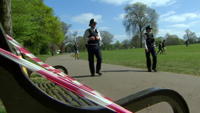 police patrol london park to ensure social distancing measures are being observed, they walk past taped off park bench - natural parkland stock videos & royalty-free footage