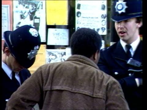 vídeos de stock, filmes e b-roll de police powers itn lib birmingham cms policeman talking to man in street cms coloured man talking to police london brixton ms two police men on beat... - brixton