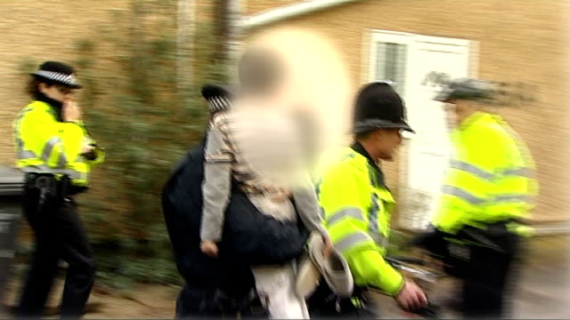 police raid gangs holding trafficked children; england: berkshire: slough: ext police officers carrying along little children rescued during raid on... - trafficking stock videos & royalty-free footage