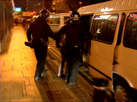 vídeos de stock e filmes b-roll de police raid in east london leads to 14 arrests; itn england: london: newham: ext/night track forwards into pub behind police dressed in riot gear int... - air raid