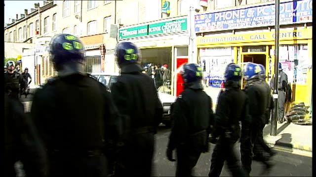 stockvideo's en b-roll-footage met police raid london street to smash stolen goods ring row of police blocking road as other police raid building police helicopter flying overhead back... - bewegingsbeperkende middelen