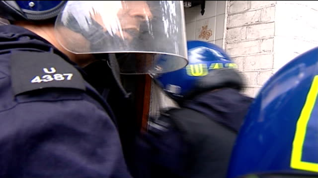 police raids ahead of notting hill carnival england london ext police officers storm through doorway into house during raid police officers seen... - クリケットバット点の映像素材/bロール