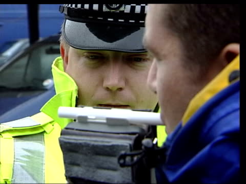 police reforms civilian officers/ vehicle crime day breathalyser held by police officer as prepared motorist taking breath test policeman and... - alkoholtest stock-videos und b-roll-filmmaterial