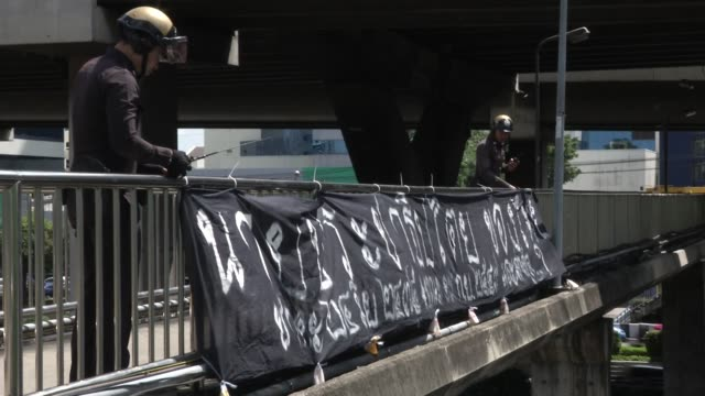 stockvideo's en b-roll-footage met police remove a banner that reads democracy in thailand birth 1932 death 2006 on a walkway near thairat newspaper on the anniversary of the 2006 coup... - staatsgreep