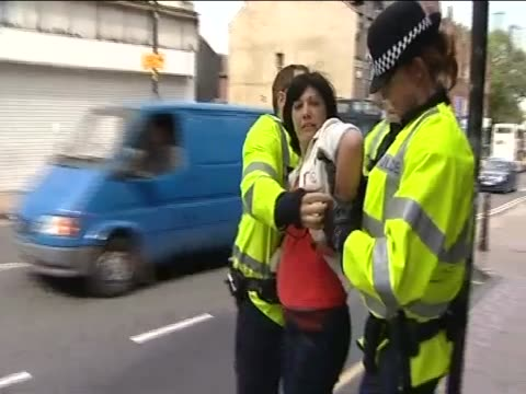 police restrain woman on the street during period of rioting in the uk august 2011 - trattenere video stock e b–roll
