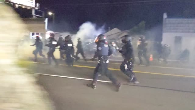 police run down the streets as tear gas and sparks drop to the ground near protesters while oregon state troopers and portland police nearby attempt... - oregon us state stock videos & royalty-free footage