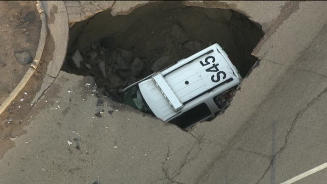 police sergeant was shaken up after a sinkhole swallowed his suv squad car on june 5, 2105 in colorado. police say the suv was entering an... - sergeant stock videos & royalty-free footage