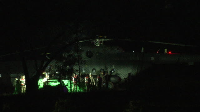 police shield a helicopter after it lands at a military base in chiang rai before transferring him to a hospital divers evacuated some of the boys... - chiang rai province stock videos and b-roll footage