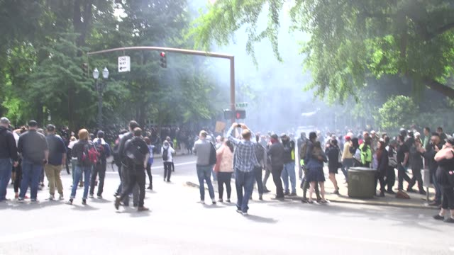 police shoot flash bangs at antifa during the portland free speech rally although it appears to emit tear gas - anti fascism stock videos & royalty-free footage