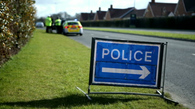 a police sign at a crime scene with police in the background - uk video stock e b–roll