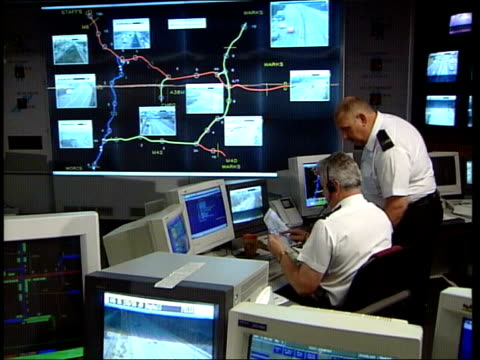 police staff working in motorway control room england midlands int gvs police staff working in motorway control room / gv road layout on large screen... - control room stock videos & royalty-free footage