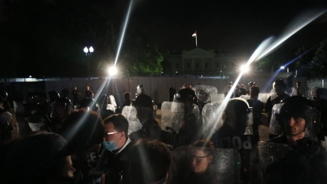 police stand behind protective shields as demonstrators chant slogans as they hold a protest in response to the police killing of george floyd in... - lafayette square washington dc stock videos & royalty-free footage