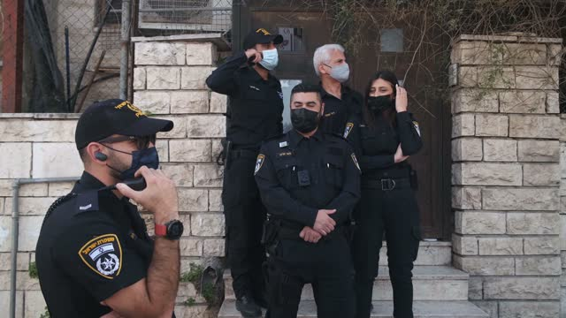 """police stand guard in front of a house which was occupied by jewish settlers as israeli left-wing activists and palestinians shout in hebrew """"stop... - judaism stock videos & royalty-free footage"""
