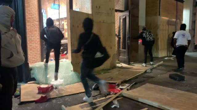 police stand guard near looted stores during a night of protests and vandalism over the police killing of george floyd on june 01, 2020 in new york... - looting stock videos & royalty-free footage