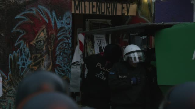 police stand outside liebigstrasse 34, also known as liebig34, and consider how to get into the building during the eviction of its residents on... - links platz stock-videos und b-roll-filmmaterial