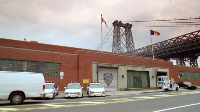 MS Police station exterior made of brick, some officers and police cars in front, street traffic traveling back and forth. bridge structure visible in background