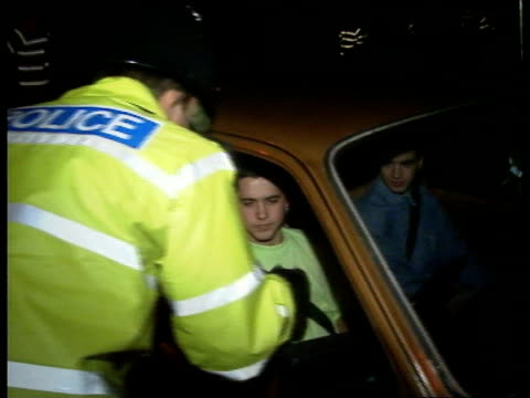 police stop acid house parties:; england: kent: gravesend: ext/night cms side policeman writing notes bv policeman taking papers from young car... - 酸点の映像素材/bロール