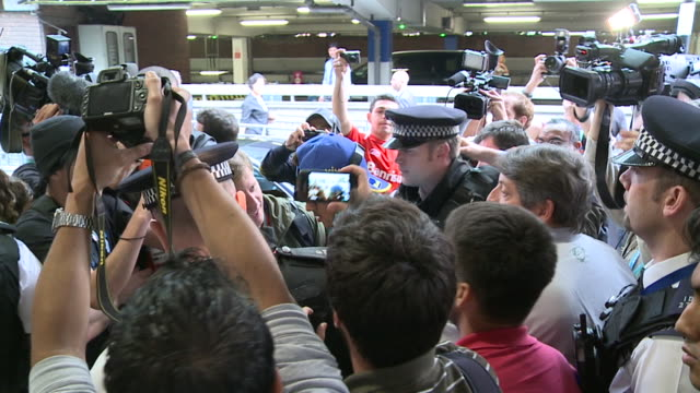 Police struggle to control media and fans as Brazil soccer team arrives for London 2012 Olympics / Huge enthusiastic crowd swamp players as they...