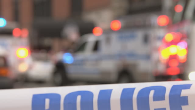 stockvideo's en b-roll-footage met ts police tape sways in front of flashing emergency vehicles in background / new york, new york, usa - afzetlint
