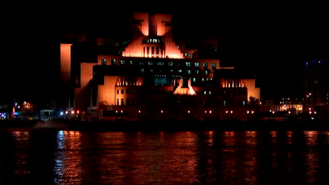 police to get temporary new anti-terrorism powers; vauxhall: ext / night lights reflecting on river thames tilt up illuminated sis building close... - mi6 stock-videos und b-roll-filmmaterial