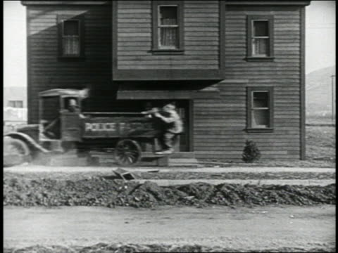 vidéos et rushes de b/w 1924 police truck destroying building supports / 2 people sleeping on bed + floor drop to ground - 1924