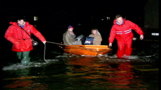 vídeos de stock, filmes e b-roll de 40 police van along through half wheel height water towyn old lady helped out of rowing boat into police van people being pulled along in row boat by... - só uma mulher idosa