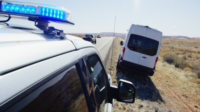 a police vehicle with its lights pulls over a large, white van on the side of the highway/interstate in the deserts of utah on a bright, sunny day - blocco stradale video stock e b–roll