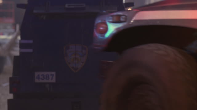 NYPD police vehicles and officers enter a crime scene.