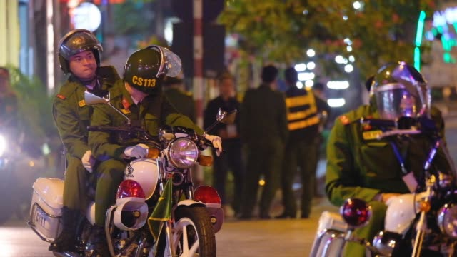police wait on motorcycles whilst us president donald trump's motorcade returns after dinner with north korean leader kim jongun before the summit on... - 首脳会議点の映像素材/bロール