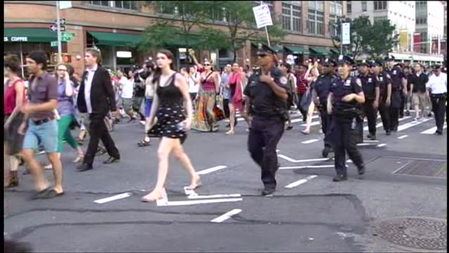 police walk alongside protesters at rally in new york city against the acquittal of george zimmerman for the murder of trayvon martin - unschuld stock-videos und b-roll-filmmaterial