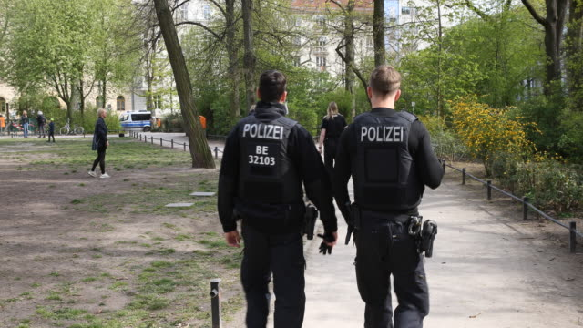 police walk through a park in the district prenzlauer berg to make sure people are not gathering in too-large groups during the novel coronavirus... - untersuchen stock-videos und b-roll-filmmaterial