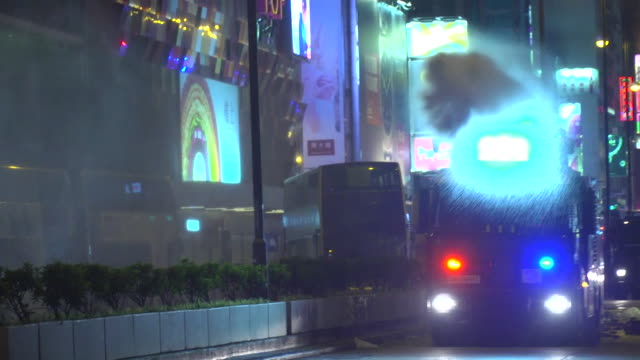 police water canon vehicle sprays water at protesters to clear streets as it drives down road at night - 放水砲点の映像素材/bロール