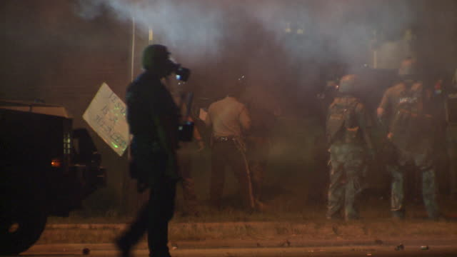 ktvi police wearing gas masks in tear gas filled streets on august 13 2014 in ferguson missouri protests and riots broke out in the town after... - missouri stock videos & royalty-free footage