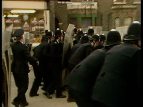 vídeos de stock e filmes b-roll de police with riot shields move forward youths run and throw stones brixton riots; 12 apr 81 - 1981