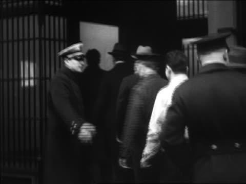 b/w 1933 policeman allowing line of men to enter liquor store / repeal of prohibition / pennsylvania - 禁酒法点の映像素材/bロール