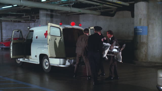 vidéos et rushes de ms policeman and attendents picking up and keeping body in ambulance at subterranean garage - ambulance
