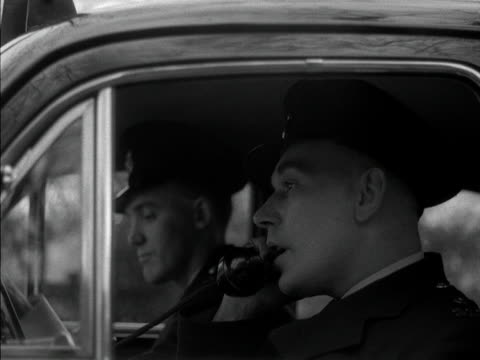 policeman answers the telephone in a police car and instructs his colleague to drive off. 1957. - veicolo di terra per uso personale video stock e b–roll
