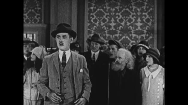 1924 policeman approaches men during citizen's arrest in hotel lobby - 1924 stock-videos und b-roll-filmmaterial