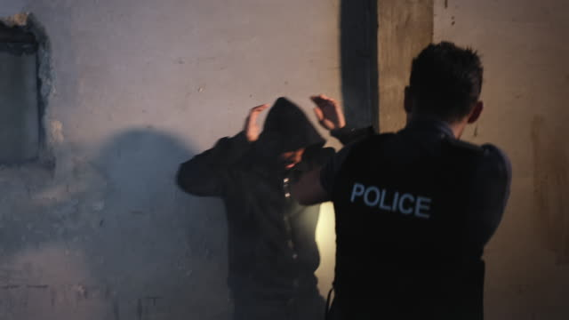 policeman arresting a suspect in an old deserted house - arrest stock videos & royalty-free footage
