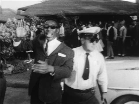 B/W 1963 policeman arresting clapping Black man with sunglasses at civil rights protest / Alabama