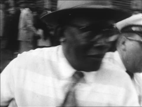 B/W 1963 policeman arresting middleaged Black man with hat at civil rights protest / Alabama / news
