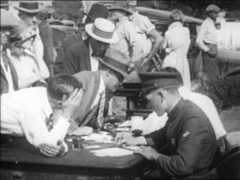 b/w 1925 policeman at table writing down names of survivors after earthquake / santa barbara ca - 1925 stock videos & royalty-free footage