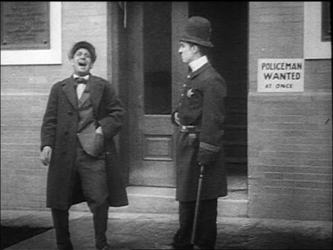 vídeos de stock e filmes b-roll de policeman charlie chaplin hitting man laughing at him with nightstick outside of station - maça