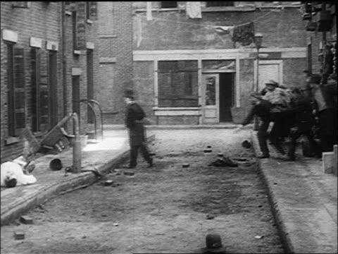 vídeos de stock, filmes e b-roll de b/w 1917 policeman charlie chaplin patrolling in city street scaring curious mob away - charlie chaplin