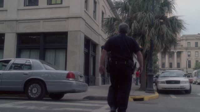 LA Policeman crossing street and walking down city sidewalk / Tybee Island, Georgia, United States